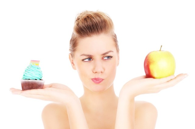 Woman holding an apple and cupcake
