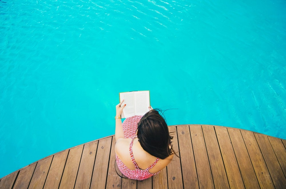 Girl reading a book by pool